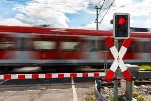 Ein Andreaskreuz mit rotem Blinklicht kündigt das Schließen der Schranke an.