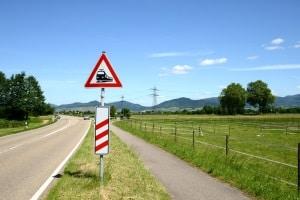 Das Verkehrsszeichen Nr. 151 zusammen mit einer Entfernungsbake: Sie kündigen den Bahnübergang an.